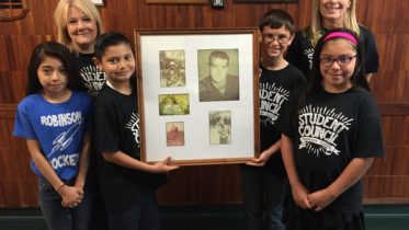 Gisselle Garcia, teacher Mary Doyle, Angel Castro, Kyle Lyth, teacher Dee Mutters and Emily Aguero, left to right, with photos of the late Sgt. James Robinson, Jr., who died a hero in Vietnam.